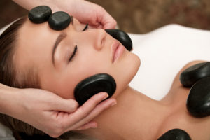 Black marble stones being placed along the face and collarbones on woman for therapy session.